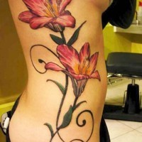 Pink lily flower tattoo on ribs