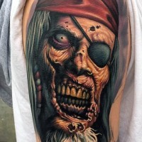 Pirate cartoon themed detailed and colored old zombie portrait tattoo on upper arm