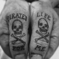 Pirate style skull with crossed bines black ink tattoo with lettering on both thumbs