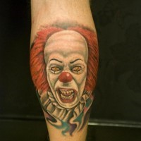 Portrait of a terrible red haired clown tattoo on leg