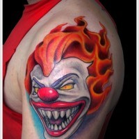 Portrait of a terrible red haired clown tattoo on shoulder