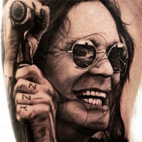 Portrait style colored famous singer face in sun glasses tattoo