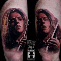 Portrait style colored thigh tattoo of famous guitar player