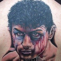Portrait style natural looking colored upper back tattoo of bloody boxers face