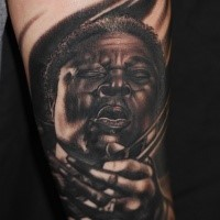 Portrait style realistic looking detailed forearm tattoo of famous guitar player