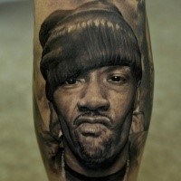 Portrait style realistic looking tattoo of thigh man face