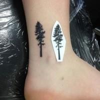 albero solitario piccolo nero su caviglia tatuaggio