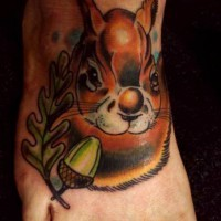 Pretty squirrel tattoo with nut on foot
