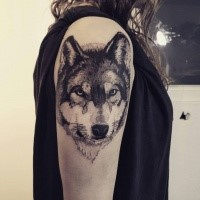 Real life like detailed upper arm tattoo of wolf portrait