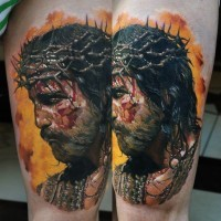 Real photo dramatic colored thigh tattoo of bloody Jesus