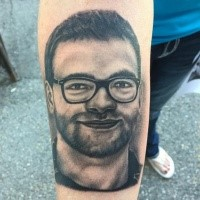 Realism style black ink forearm tattoo of man in sun glasses