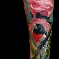 Realism style colored arm tattoo fo beautiful bird with pink flowers
