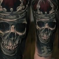 Realism style colored arm tattoo of human skull with crown