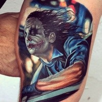 Realism style colored biceps tattoo of creepy Joker