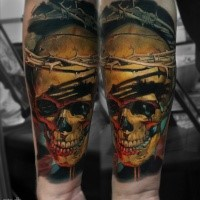 Realism style colored forearm tattoo of bloody human skull with vine