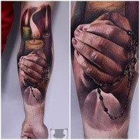 Realism style colored forearm tattoo of praying hands with candles