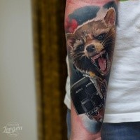 Realism style colored raccoon with fantasy gun tattoo on forearm