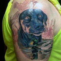 Realism style colored shoulder tattoo of hunters dog with ducks