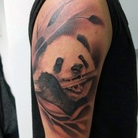 Realism style colored shoulder tattoo of panda bear with bamboo