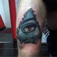 Realism style colored thigh tattoo of mystic eye and leaves