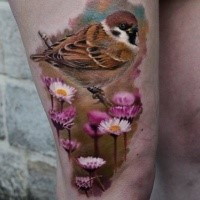 Realism style colored thigh tattoo of little bird with flowers