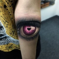 Realism style colored woman eye stylized with small black heart forearm tattoo