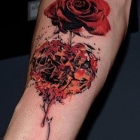 Realism style red colored rose tattoo on forearm with heart