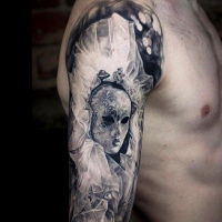 Realistic black and white  mask tattoo on shoulder