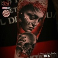 Realistic looking colored arm tattoo of woman face with skull