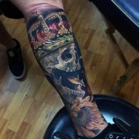 Realistic looking colored leg tattoo of skull with crown and flower