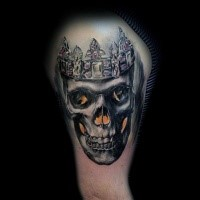 Realistic looking colored shoulder tattoo of human skull with crown