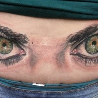 Realistic looking colored tattoo of creepy evil woman eyes