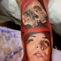 Realistic painted and colored woman in red hood with human skull tattoo on arm