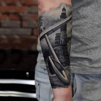 Realistic photo like black and white old anchor with light house tattoo on arm