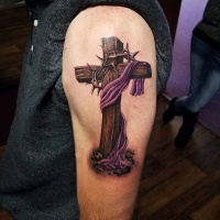 Realistic wooden cross with barbed wire and purple cloth tattoo