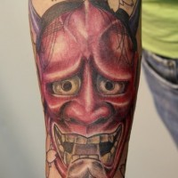Red demon tattoo on arm