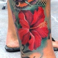 Red hibiscus flower with butterfly tattoo on leg