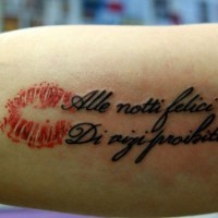 Red kiss and italian quote tattoo on arm