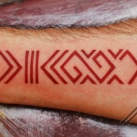 Red latin symbol forearm tattoo
