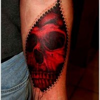 Red skull looks out of skin rip forearm tattoo