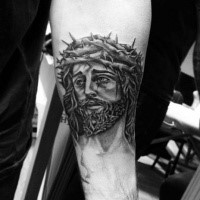Religious Jesus Christ portrait in crown of thorns tattoo on forearm