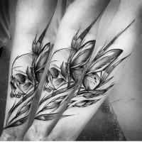 Romantico inchiostro nero dipinto da Inez Janiak tatuaggio avambraccio di teschio umano con farfalla e foglie