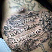 Romantic style nautical themed black ink tattoo with steering wheel and lettering on chest