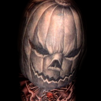 Scary Halloween pumpkin and memorial date on banner shoulder tattoo with tiny skull