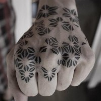 Simple black and white geometric flower shaped tattoo on fist