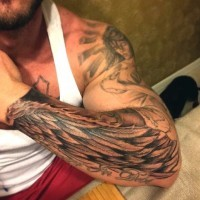 Simple black ink detailed wing with lettering tattoo on arm