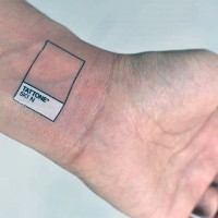 Simple black ink frame with lettering tattoo on wrist