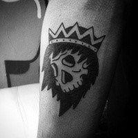 Simple black ink human skull with crown tattoo on forearm