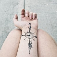 Simple black ink nautical compass tattoo on wrist