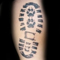 Simple black ink tattoo of human foot print combined with small dag paw prints